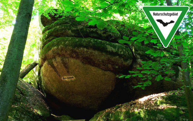 The Froschmaul rock formation in Falkenstein Schlosspark, Germany, with nature reserve sign