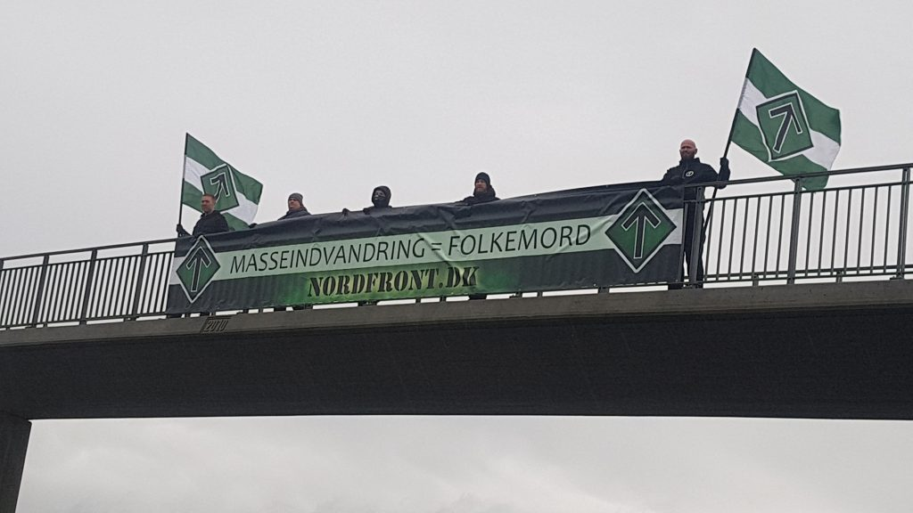 "Nordic Resistance Movement activists hold a ""Mass Immigration Is Genocide"" banner over a bridge in Denmark"