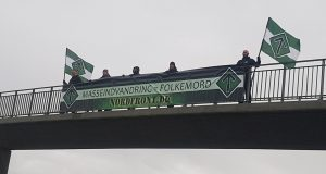 """Nordic Resistance Movement activists hold a """"Mass Immigration Is Genocide"""" banner over a bridge in Denmark"""