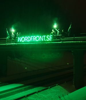 Nordic Resistance Movement members hold a glowing banner atop a bridge in Ludvika, Sweden
