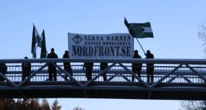 """Nest 5 Nordic Resistance Movement activists hold a banner reading """"Protect the Children – Crush the Homo Lobby"""" on a bridge in Borlänge, Sweden"""