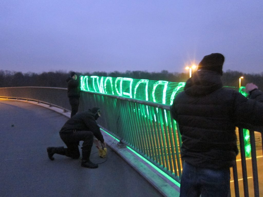 Danish Nordic Resistance Movement activists advertise the branch's website with a glowing LED banner in Glostrup, Copenhagen