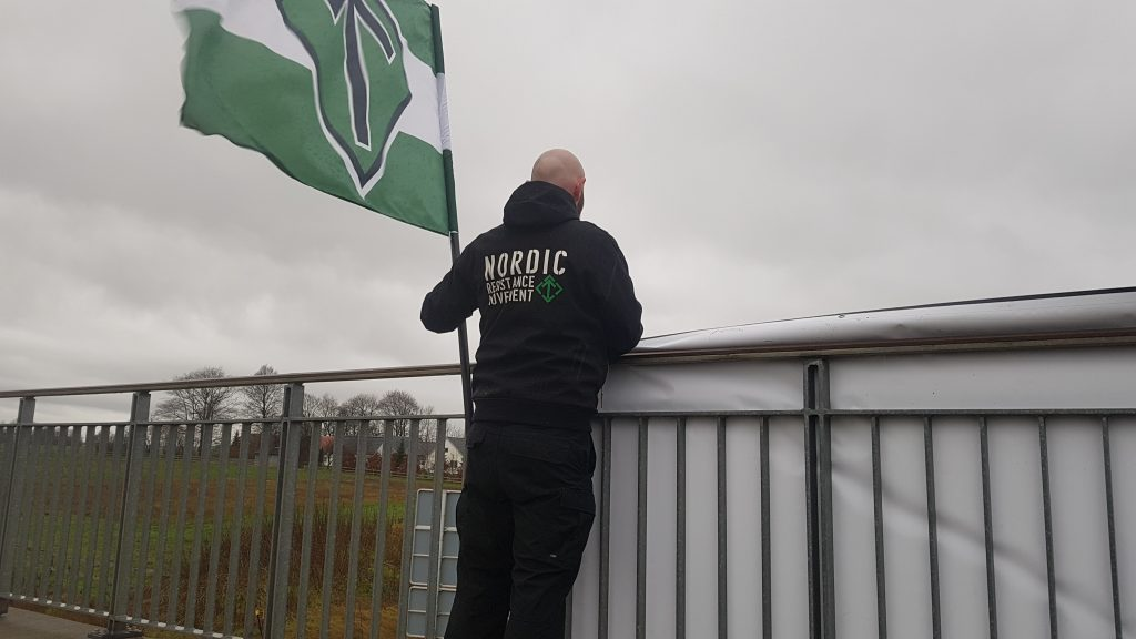 A Nordic Resistance Movement activist holds a Tyr Rune flag on a bridge in Bording, Denmark