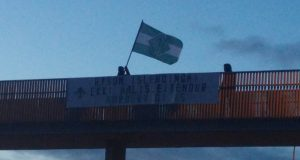 Nordic Resistance Movement members in Iceland hold a banner and flag on a bridge