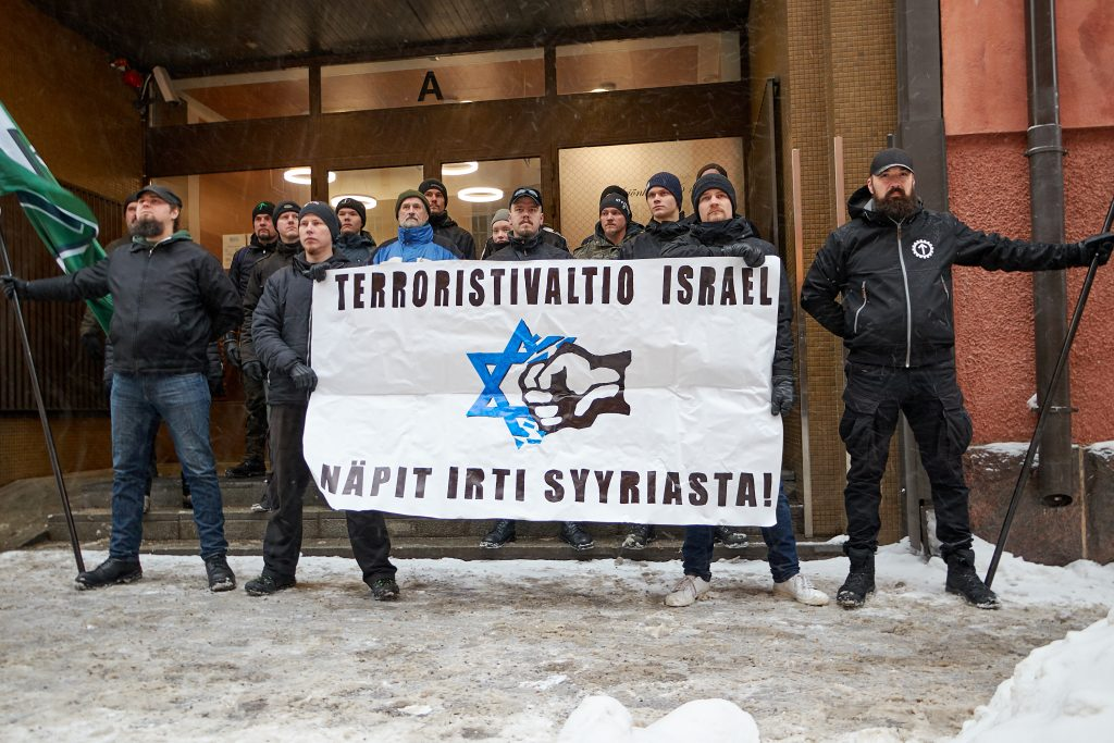 "Members of the movement holding a banner that says ""Terrorist state of Israel — Keep your hands off from Syria!"""