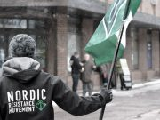 A Nordic Resistance Movement member holds a Tyr Rune flag in Horten, Norway