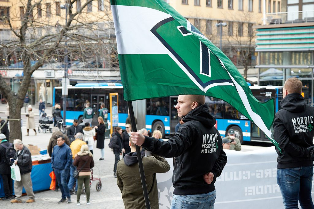 A Nordic Resistance Movement activist holds a flag in Stockholm