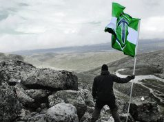 Man holds a Nordic Resistance Movement flag in the mountains