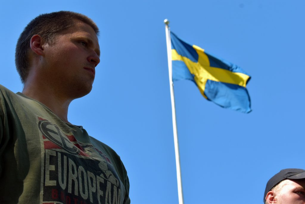 Nordic Resistance Movement activist in front of Swedish flag