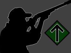 Silhouette of man shooting rifle