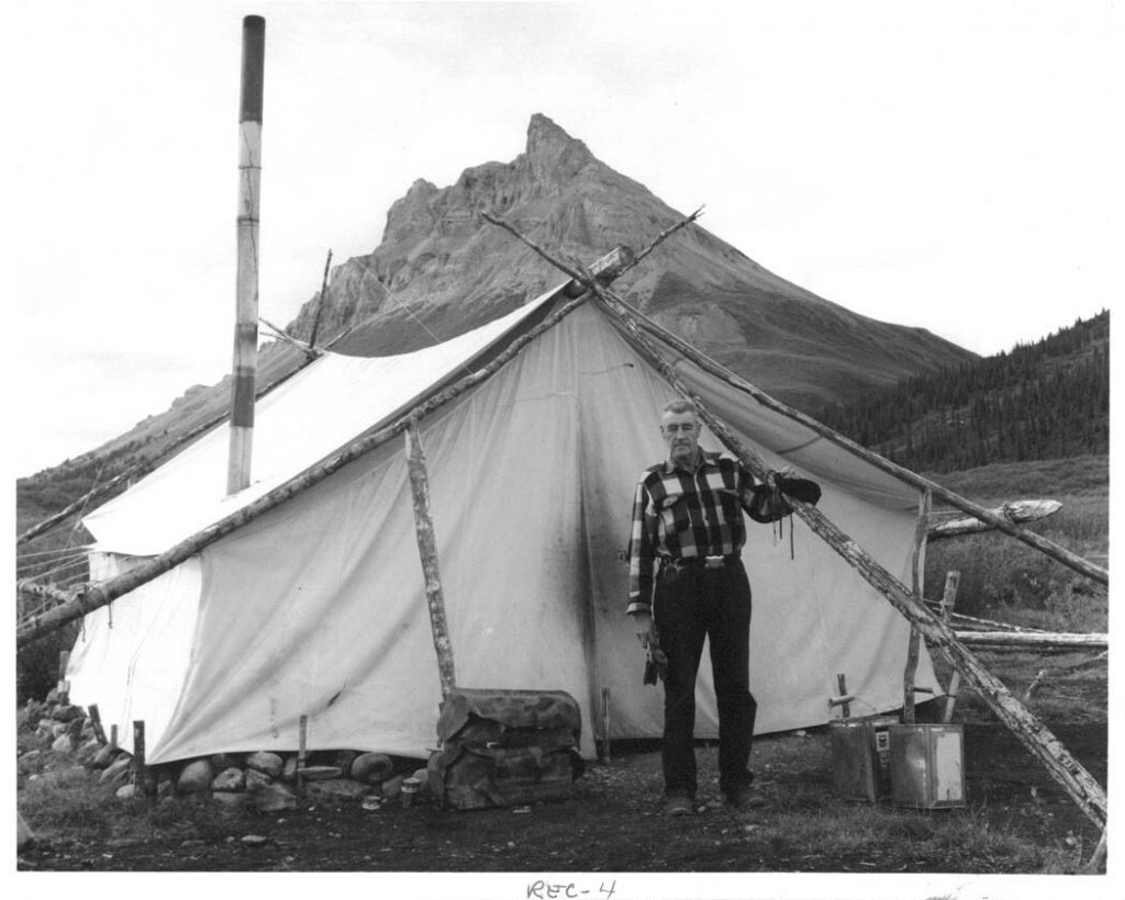 Black and white photo of a man and a tent
